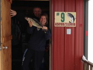 two people with fish in doorway red fish house
