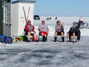 four people sit outside on frozen lake
