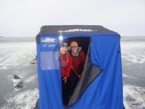 Two girls peek out Ice Lodge