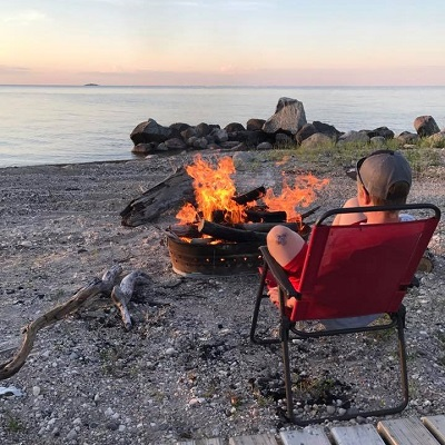 Boy sitting in red chair by campfire