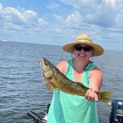 Woman in boat holds up fish