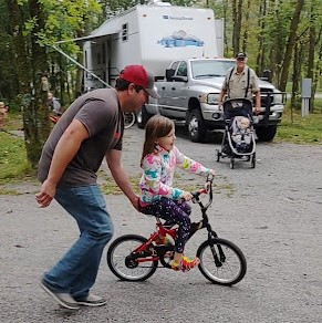 Little girl learns to ride bike with help from dad