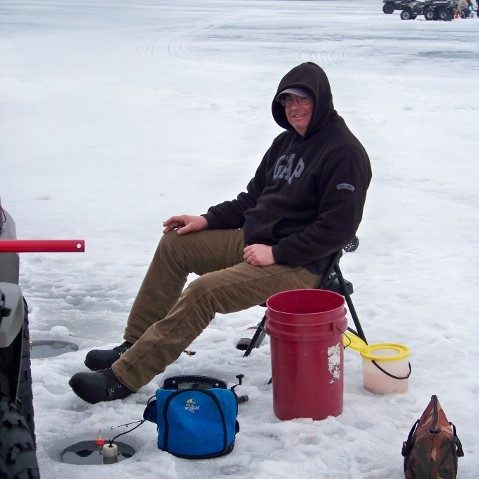 man ice fishing with red bucket
